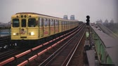rotaie : The yellow metro train arrives at the ground station on the bridge across the wide Dnieper River in Kiev. Filmati Stock