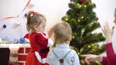 preocupacion : baby and pregnant mom hang red ball toy on Christmas tree. happy childhood concept. child and mother decorate tree with christmas balls. small child and a parent are playing by Christmas tree. Archivo de Video