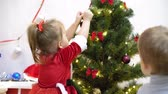 aggodalom : baby and pregnant mom hang red ball toy on Christmas tree. happy childhood concept. child and mother decorate tree with christmas balls. small child and a parent are playing by Christmas tree. Stock mozgókép