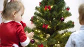 preocupacion : baby and pregnan mom hang red ball toy on Christmas tree. happy childhood concept. child and mother decorate tree with christmas balls. small child and a parent are playing by Christmas tree.