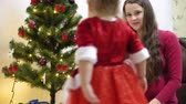 aggodalom : baby and pregnan mom hang red ball toy on Christmas tree. happy childhood concept. child and mother decorate tree with christmas balls. small child and a parent are playing by Christmas tree.