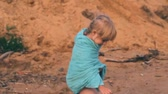 rest : little girl plays in sand on the bank of a reservoir