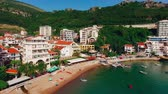 junho : Settlement Rafailovici, Budva Riviera, Montenegro. The coast of the city on the Adriatic Sea. Aerial photography. Boats at sea, hotels, villas and apartments on the coast.