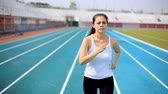 dürtmek : Woman running  on stadium track Stok Video