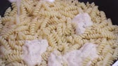 helezon : Pouring pasta and cooking in nonstick pan, stock footage