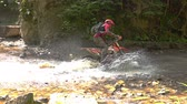 Enduro Motocycle Rider Crosses Mountain River Splashes of Water and Dirt. Slow Motion. Стоковые видеозаписи