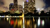 negócio : Time lapse footage with tilt up motion of downtown Los Angeles Skyline over water reflection at night with incoming clouds Stock Footage