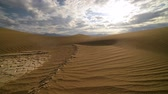 wydmy : Footage with pan right motion of clouds over desert sand dunes at sunrise in Death Valley National Park, California Wideo