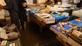 Footage of people shopping for fresh seafood product at Tsukiji Fish Market district in Tokyo, Japan -pan right-