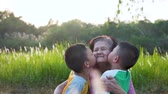 jovial : Boy grandson kiss their beloved grandmother on both sides.