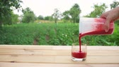 transfuse : transfusion strawberry smoothie from measuring cups into a glass
