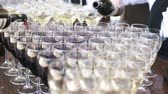 banquette : The waiter pours red wine in the rows of glasses at the festival Stock Footage