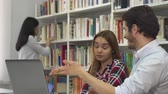 convince : Two caucasian students arguing about something on laptop. Pretty brown haired girl disagreeing with her male classmate. Handsome bearded guy trying to convience his female friend at the library Stock Footage