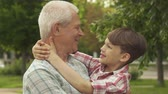 little : Attractive little boy holding his hands behind his grandpas neck against background of green trees and grass. Slow motion of senior gray man holding his grandson in his arms. Close up of brunette caucasian kid and his grandfather looking at each others fa Stock Footage