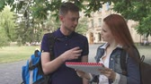 campus : Two cute students discussing something in notebook on campus. Handsome blond guy talking to his pretty female classmate. Cute caucasian redhead girl and her male friend standing under the tree against background of some building Stock Footage