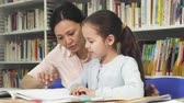 oktatói : Cute little girl doing homework with her mother