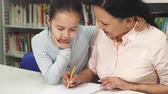 Happy mature Asian woman helping her little daughter with studying Stock Footage