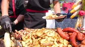 osoba : Street Food Festival. A chef in black clothes and gloves spreads fried food on plates. Potatoes, grilled sausages, meat with sticks, barbecue. Food close up