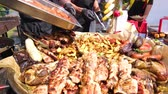 osoba : Street Food Festival. A chef in black clothes and gloves adds a new batch of sausages. Potatoes, grilled sausages, meat with sticks, barbecue. Food close up. Wideo
