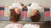 hádka : Little brother and sister lying on the bed hanging his head down laugh.