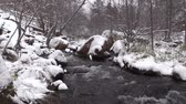 климат : Stream Flows Through Snow Covered Landscape