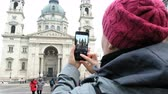 vzít : BUDAPEST, HUNGARY - 18 JANUARY, 2019: Woman tourist making photo of St. Stephens Basilica by mobile. Budapest, Hungary