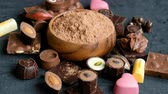Assorted chocolate and cocoa on black background, close up. High angle view Vidéos Libres De Droits