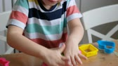 教育 : Lovely 4 years boy with playdough at home. Hands close up