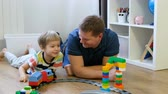 Family concept. Boy and dad playing with trains on wooden floor. Father with son Vidéos Libres De Droits