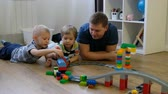 Family concept. Boys and dad playing with trains on wooden floor. Father with sons Vidéos Libres De Droits