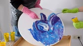 нефтяной : Woman making fluid art acrylic painting. Creative cosmic artwork hippie wallpaper in blue color with hands of creator. Стоковые видеозаписи