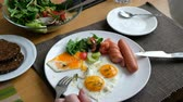 ungesund : Man eating breakfast. Knife and fork in hand. American style breakfast with fried eggs, sausage, salad and toast. Stock Footage