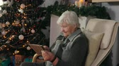 comunicação : Elderly woman reads the message on a plate next to Christmas tree Stock Footage
