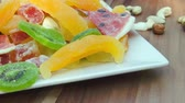 copy : Plate of nuts and candied fruit kiwi, orange, watermelon, mango and pineapple