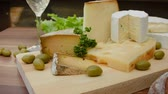 borgonha : Circular movement of the camera around of Pieces of cheese on a wooden board with white wine, bread and olives