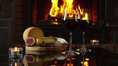 темно бордовый : Hand puts on the table a glass of red wine. Reflection of the fire in the fireplace glass table with wine and snacks