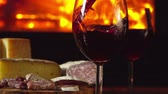 темно бордовый : Close-up Red wine is poured into glasses on the background of snacks around fireplace