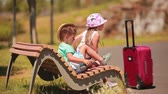 suitcases : Boy and girl resting on a bench after a long road with a suitcase Stock Footage