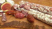 kırmızı biber : Circular movement of the camera around uncooked jerked sausages, baguette and figs on a wooden board