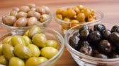 farmers market : Several kinds of olives in glass bowls with greenery