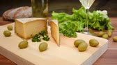 úsek : Unpasteurised, semi-hard cheese made from sheeps milk with natural, crusty, brownish rind on a wooden board with herbs on background Dostupné videozáznamy