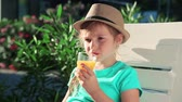 блины : Boy drinking orange juice. Boy in a hat on the beach Стоковые видеозаписи