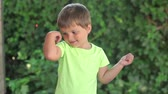 победитель : Little boy shows his muscles on the open veranda