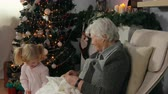 emaranhado : Grandmother knits a sock while sitting in a chair next to the Christmas tree. The little girl holds a ball