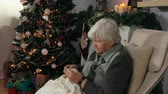 emaranhado : An elderly woman knits a blanket sitting in a chair next to the fireplace near the Christmas tree