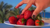 high speed camera : Hand takes a large juicy strawberry from a white plate against the background of the sunny sea landscape