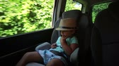 kierownica : A little boy in a hat looks through the open window while the car is moving.