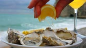 устрица : Hand squeezes lemon juice on fresh oysters against the background of ocean waves on the quay Etretat, Normandy