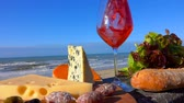 каберне : Romantic picnic with Normandy cheese and snack on a wooden board in front of the Surf of the Atlantic Ocean. Red wine is poured into a wine glass