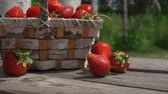 džem : Strawberry fall on a wooden table next to a wicker basket. Slow shooting in the open air against the background of birches